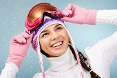 picture of knitted cap  - Cheerful woman in goggles and knitted winter cap captured by snowfall - JPG