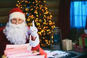 Happy Santa Claus looking at camera with raised forefinger