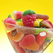 closeup of a pile of different candies in a glass on a yellow background