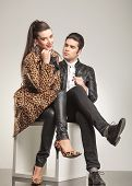 Beautiful young fashion woman sitting with her legs crossed, holding her hand to her chin while her lover is sitting and looking at her.