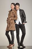 Full length picture of a young fashion couple posing for the camera, both holding hands in pockets.