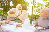 Senior woman bringing gift to birthday party in a summer garden