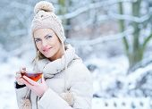 Smiling woman drinking a cup of hot black tea in winter snow