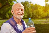 Thirsty senior man drinking fresh water after sports