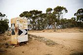 image of dirt road  - An old rusted fridge turned into a country road sign with gum trees and dirt road - JPG
