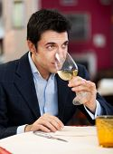 Handsome man drinking a glass of wine