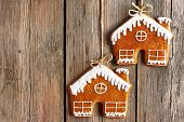 Christmas homemade gingerbread house cookies over wooden background