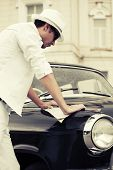 Young fashion man with a road map at the retro car