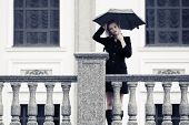 Fashion young woman with umbrella in the rain