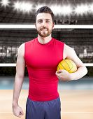 Volleyball player on red and blue uniform on volleyball court.