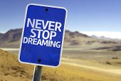 Never Stop Dreaming sign with a desert background