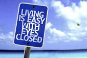 Living is Easy With Eyes Closed sign with a beach on background