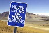 Never Let Go Of Your Dreams sign with a desert background