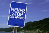 Never Stop Dreaming sign with a beach on background