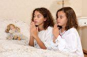 Adorable victorian girls kneeling in their vintage bedroom and praying