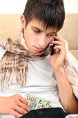 pic of home remedy  - Sick Teenager with Cellphone checking the Wallet on the Sofa at the Home - JPG
