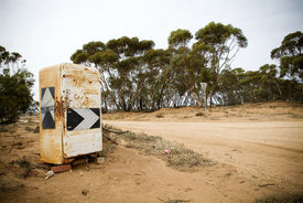 picture of dirt road  - An old rusted fridge turned into a country road sign with gum trees and dirt road - JPG