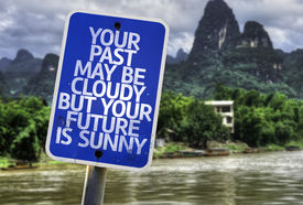 stock photo of past future  - Your Past May Be Cloudy But Your Future is Sunny sign with a exotic background - JPG