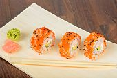 picture of masago  - Closeup California maki sushi with masago on the wooden plate - JPG