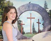 pic of he is risen  - A pretty teen girl delighted before an Easter resurrection display - JPG