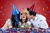 pic of birthday hat  - Young asian family wearing birthday cap and kissing the child in birthday party - JPG