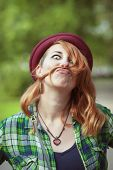 image of moustache  - Hipster redhead woman making a moustache with her hair outdoor - JPG