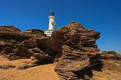 pic of lighthouse  - Photo of the Point Lonsdale Lighthouse taken from the Beach showing the Rocks below the Lighthouse. Point Lonsdale is Located in Victoria Australia. - JPG