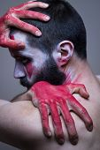 stock photo of cold-shoulder  - Bearded man with red painted hands embracing himself - JPG