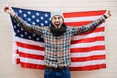 pic of macho man  - Excited young man holding American flag while standing against brick wall - JPG