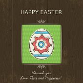 picture of easter card  - Hand painted easter egg in the green square. Brown wooden background and greetings inscription Happy 