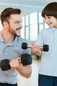 image of physical education  - Happy father and son exercising with dumbbells while both standing in health club together - JPG