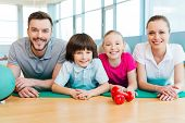 pic of family bonding  - Happy sporty family bonding to each other while lying on exercise mat together - JPG