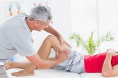 picture of thighs  - Man having thigh massage in medical office - JPG