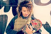 picture of rasta  - portrait of young guy with skateboard and rasta hair in a lifestyle concept warm filter applied - JPG