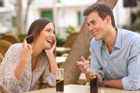 stock photo of candid  - Couple dating and flirting while taking a conversation and looking each other in a restaurant - JPG
