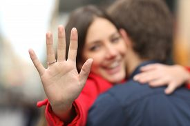 pic of cuddle  - Happy woman looking engagement ring after proposal while is cuddling her boyfriend in the street - JPG