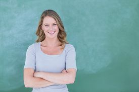 stock photo of classroom  - Smiling teacher standing in front of blackboard in classroom - JPG