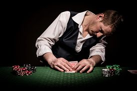 image of gambler  - A male gambler checks once his cards on the table before placing the bet - JPG