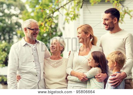 family, happiness, generation, home and people concept - happy family standing in front of house out