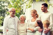 family, happiness, generation, home and people concept - happy family standing in front of house out poster