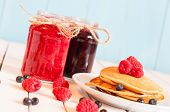 foto of mason  - Stack of wheat golden pancakes or pancake cake with freshly picked raspberries on a dessert plate - JPG