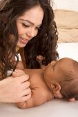 Latina Mother Playing With Her Baby Boy Son On Bed