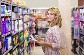 stock photo of supermarket  - Portrait of a smiling pretty blonde woman writing on a notepad in supermarket - JPG