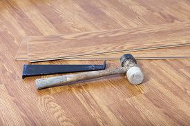 stock photo of laminate  - Hammer pull bar and laminate floor boards on top of finished laminate wood floor - JPG