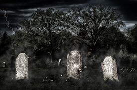 foto of headstones  - Weathered headstones in an old cemetery glow in an eerie light in the gloom with a grainy sky and fog wisps - JPG