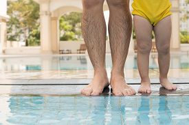 image of wet pants  - Man with little son standing at poolside - JPG
