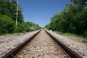 stock photo of train track  - Railway tracks disappear into the horizon under a blue sky - JPG