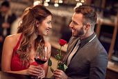 Handsome man giving rose to attractive lady poster