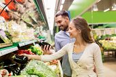 shopping, food, sale, consumerism and people concept - happy couple buying avocado at grocery store  poster