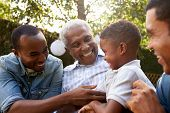 Black grandfather, sons and grandson talking in a garden poster
